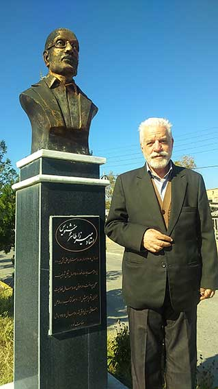 دکتر حسین محمدزاده صدیق در کنار مجسمه میرزا طاهر خوشنویس- روستای سیه رود